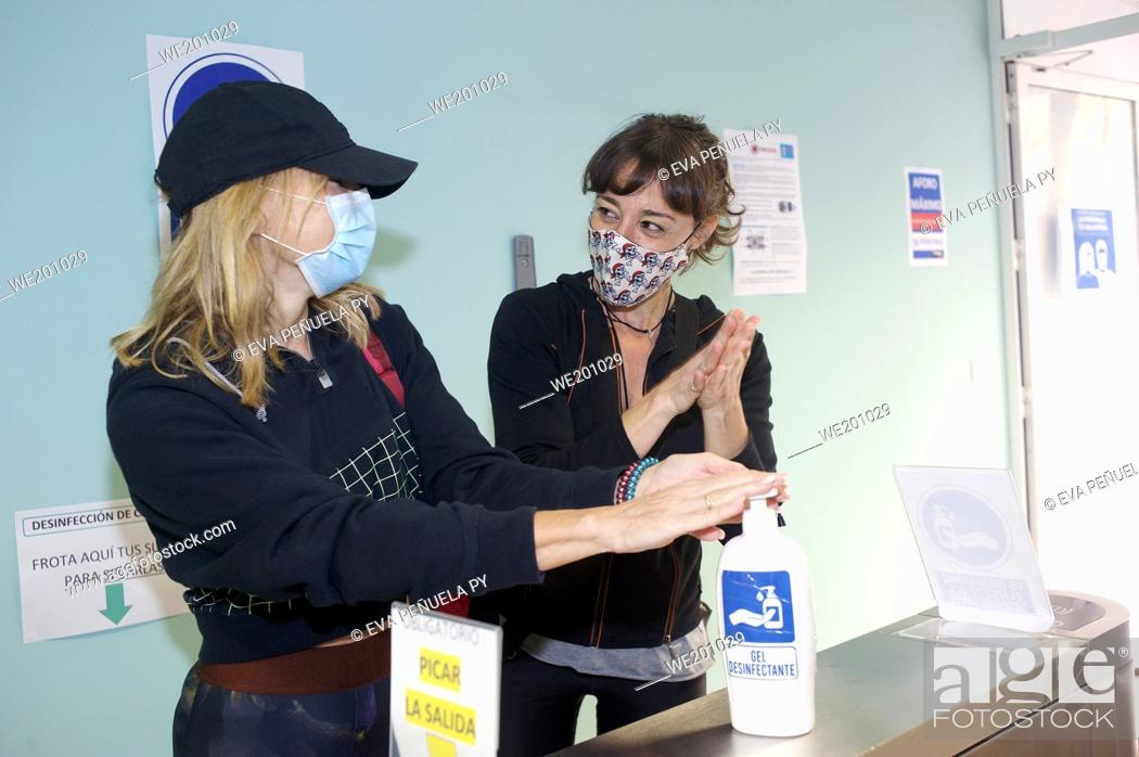 Stock Photo: Two friends with masks sanitizing hands with hydrogel.