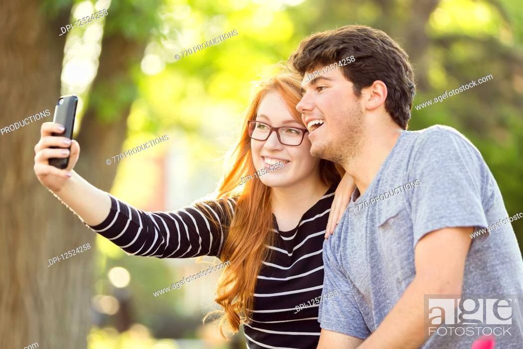 Stock Photo: A young man and young woman taking a self-portrait on a smart phone; Edmonton, Alberta, Canada.