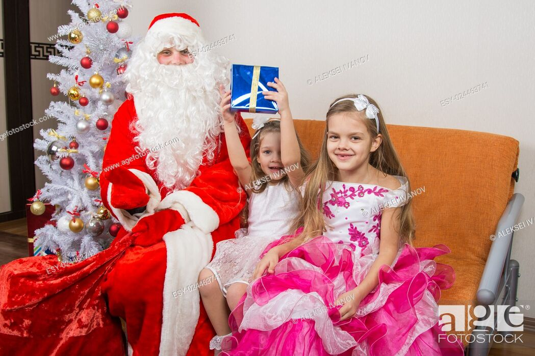 Stock Photo: Santa Claus presented the first gift girls.