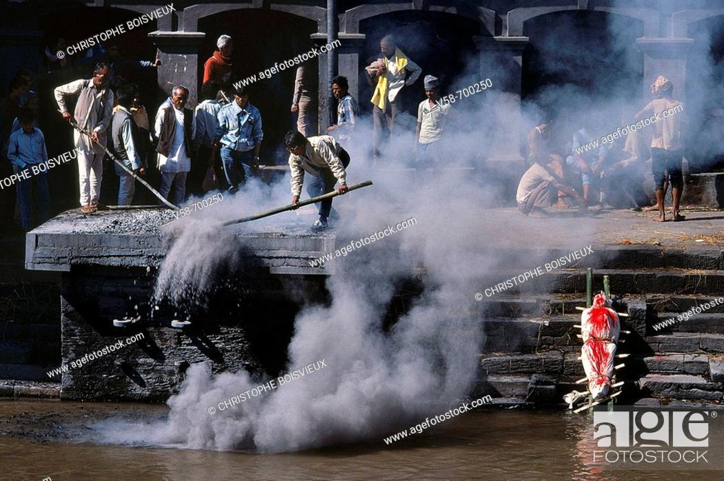 Attendants throwing ashes into bagmati river after a