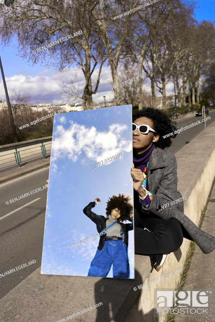 Stock Photo: young man holding mirror reflecting woman, in Paris, France.