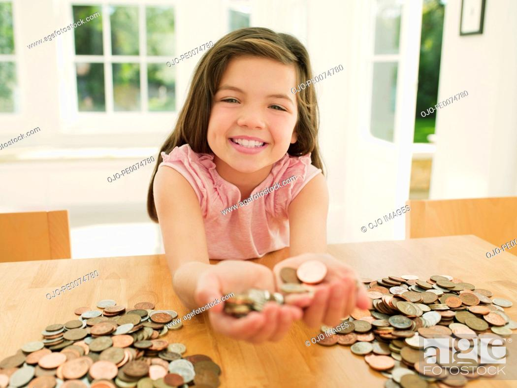 Stock Photo: Smiling girl holding handful of coins.