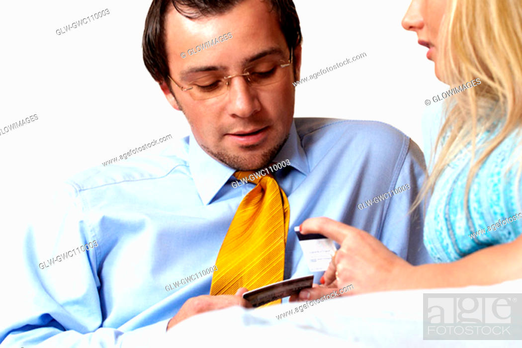 Stock Photo: Businessman and a businesswoman looking at credit cards.