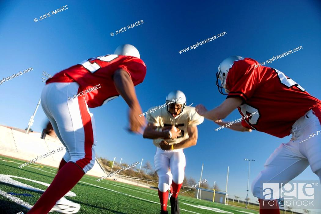 Stock Photo: American football player running with ball at opposing team during competitive game surface level, tilt.