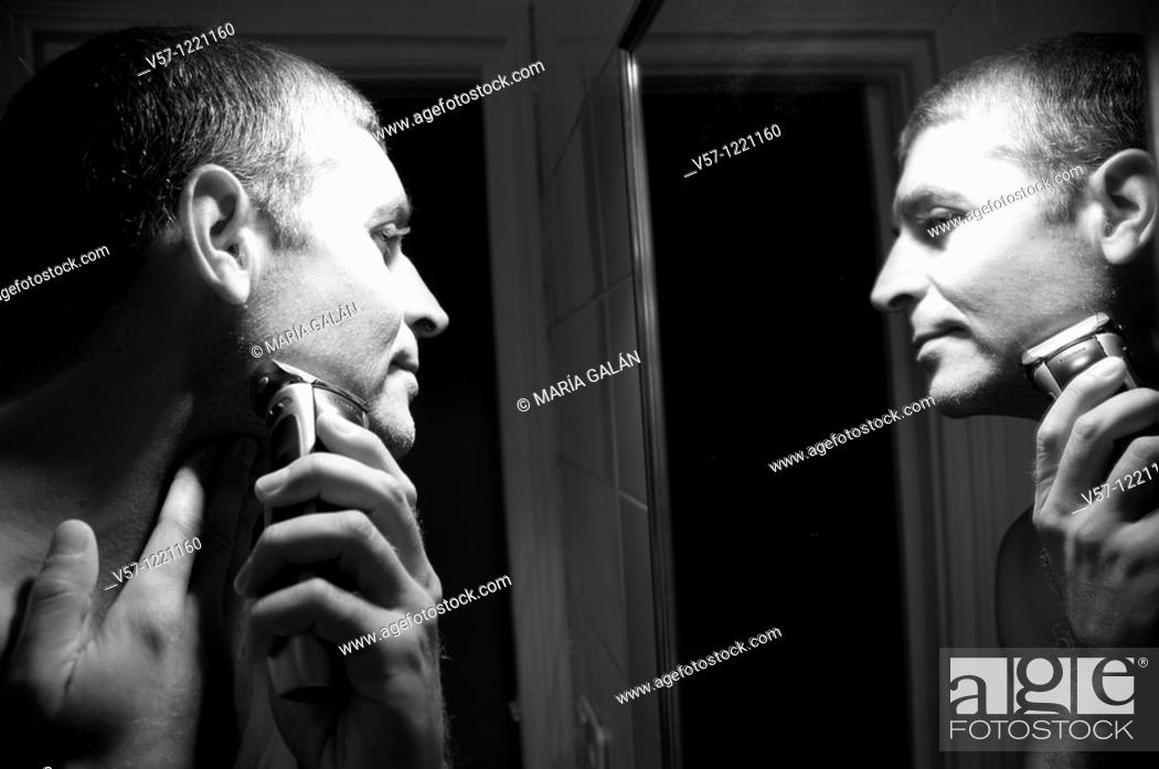 Stock Photo: Man shaving his face in front of mirror. Black and white.