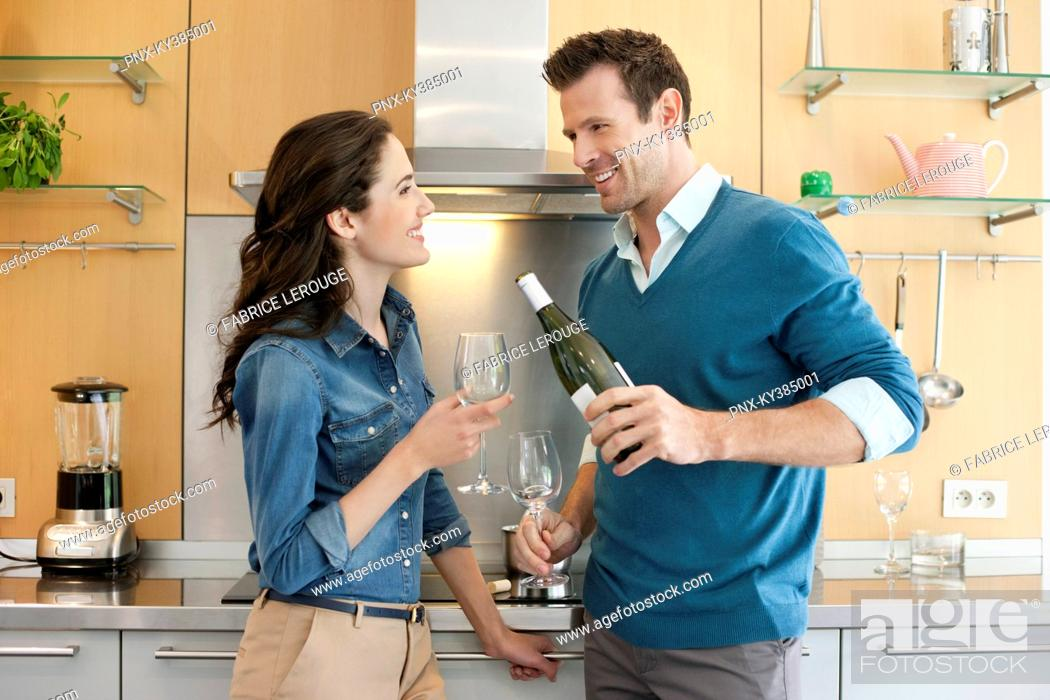 Stock Photo: Couple drinking wine in the kitchen.
