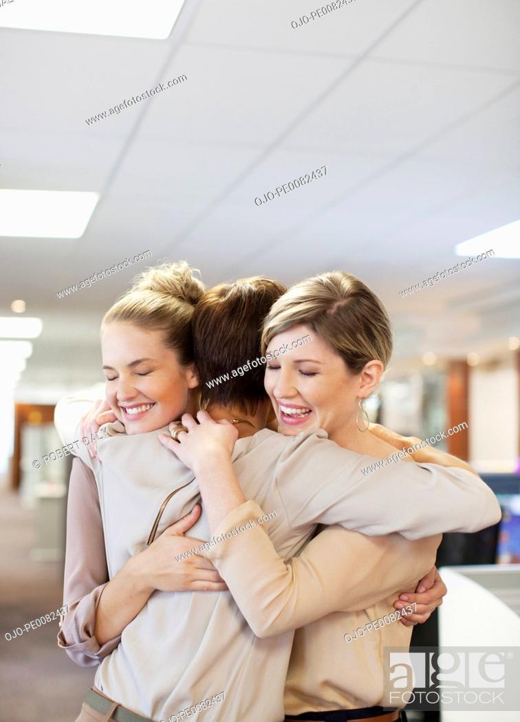 Stock Photo: Happy businesswomen hugging in office.