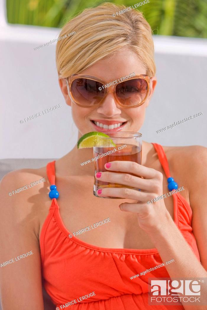 Stock Photo: Woman holding a glass of cola.