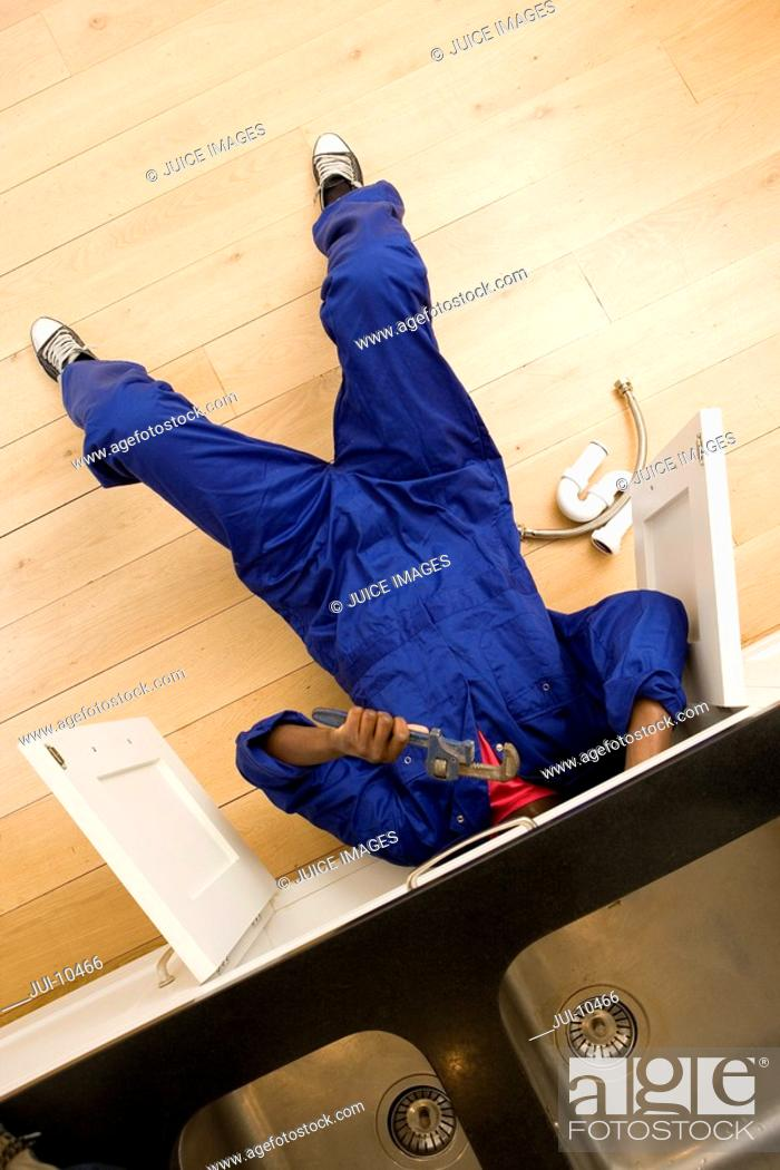 Stock Photo: Plumber working under kitchen sink, overhead view.