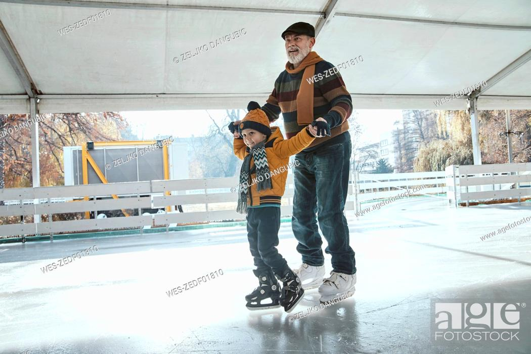 Stock Photo: Grandfather and grandson on the ice rink, ice skating.