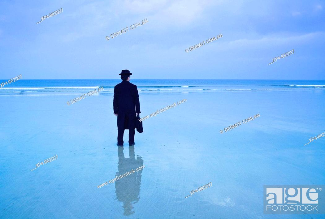 Stock Photo: Man standing on the beach in black hat and overcoat with briefcase looks out to the ocean, his image reflected in the wet sand.