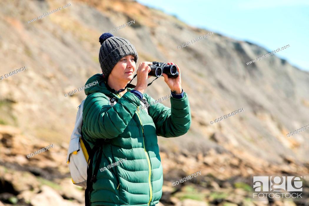 Stock Photo: Woman using binoculars on rock, Folkestone, UK.