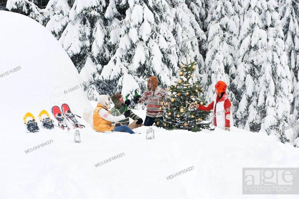 Stock Photo: Austria, Salzburg, Men and women sitting by christmas tree in winter.