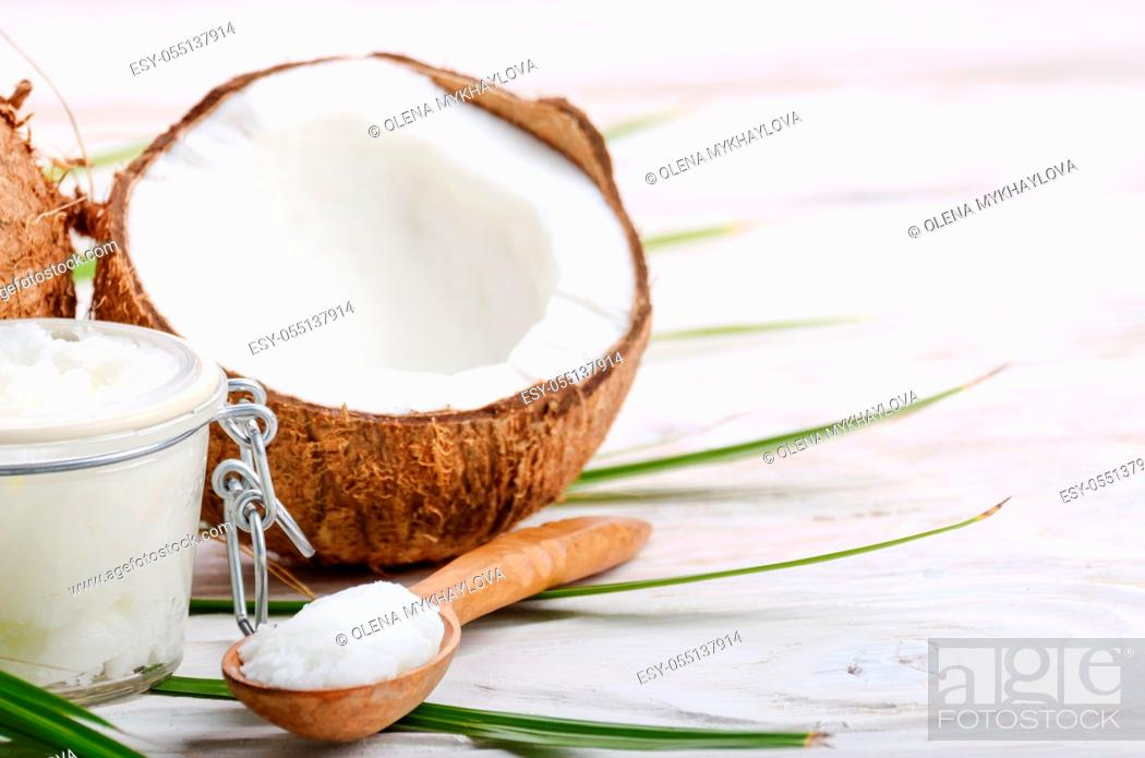 Stock Photo: Coconut oil in airtight glass jar spoon and shell pieces on white wooden table.