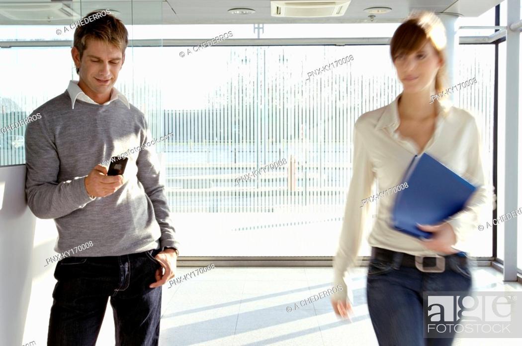 Stock Photo: Businesswoman walking beside a businessman at an airport.