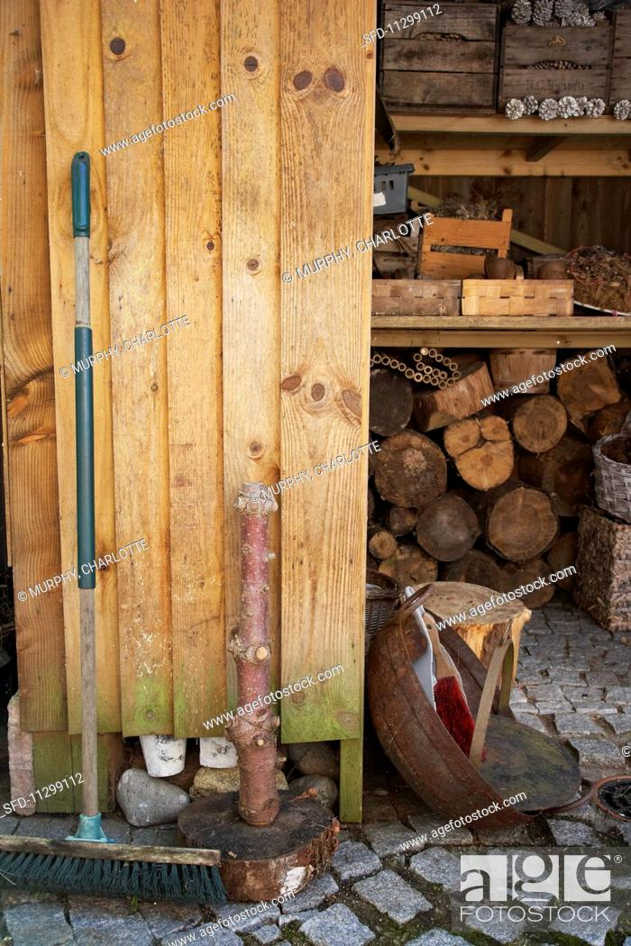 Stock Photo: An old broom leaning against a wooden wall in front of a wood shed with crates on a shelf above.