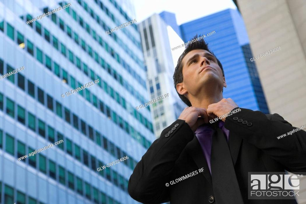 Stock Photo: Low angle view of a businessman loosening his tie.