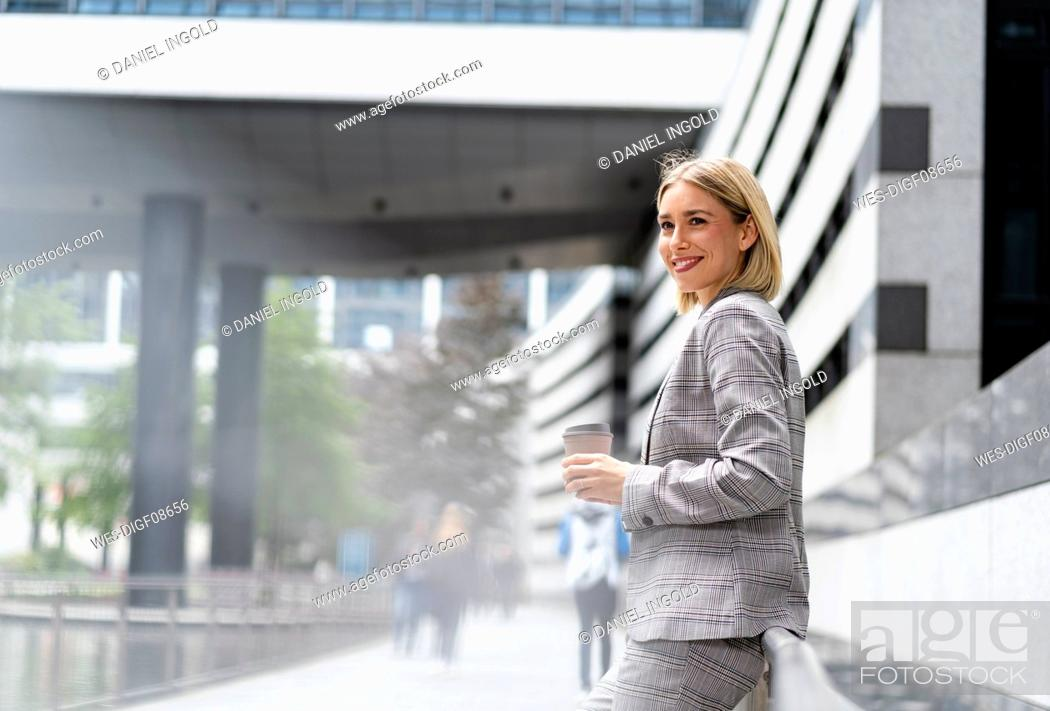 Stock Photo: Smiling young businesswoman with takeaway coffee in the city.