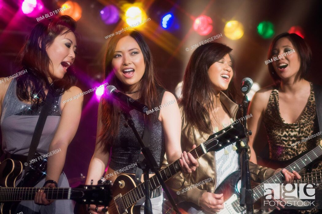 Stock Photo: Asian women singing and playing electric guitar onstage.