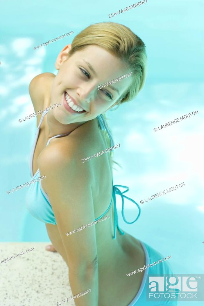 Stock Photo: Young woman raising self up on edge of pool.