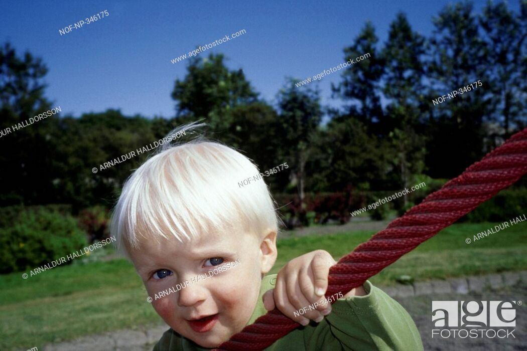 Stock Photo: A boy climbing on a rope in a playground.