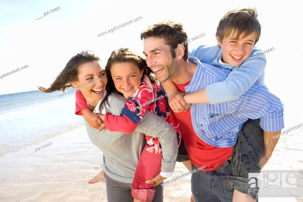 Stock Photo: Parents piggybacking children on beach.