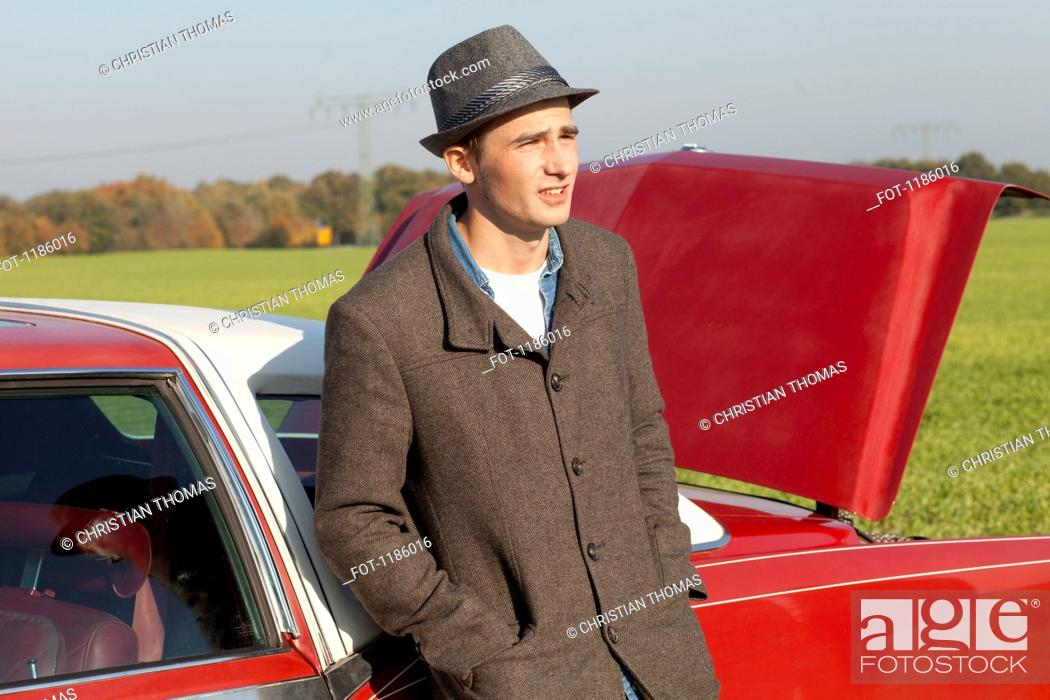 Stock Photo: A young rockabilly man leaning against a vintage car in the country.
