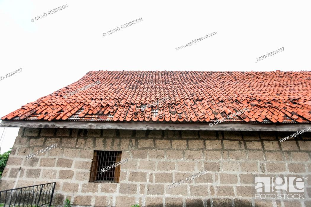 Stock Photo: House with tiled roof and stone wall in Manila, Philippines.