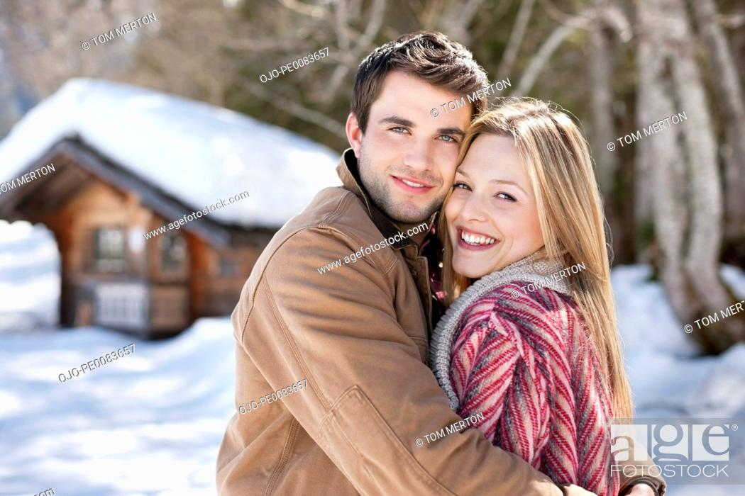 Stock Photo: Portrait of smiling couple hugging in front of cabin.