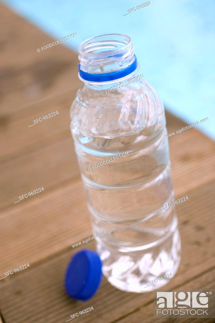Stock Photo: Bottle of water by swimming pool.