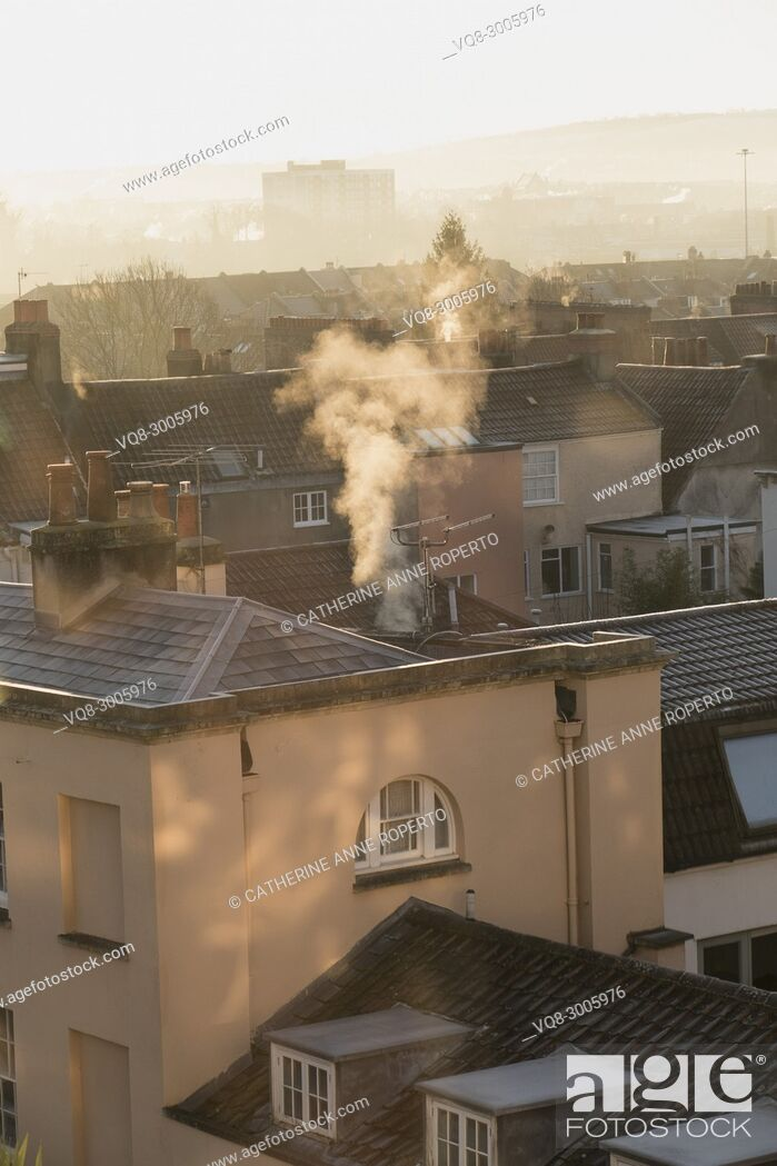 Imagen: Dappled sunlight and plumes of white smoke curling upwards on a frosty day from the historic rooftops of Hotwells, Bristol, England.