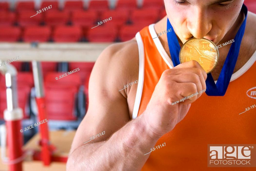 Stock Photo: Male gymnast kissing gold medal around neck, close-up.