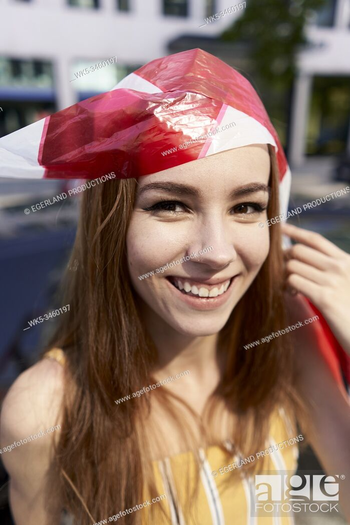 Stock Photo: Young woman tangled in caution tape. Munich, Germany.