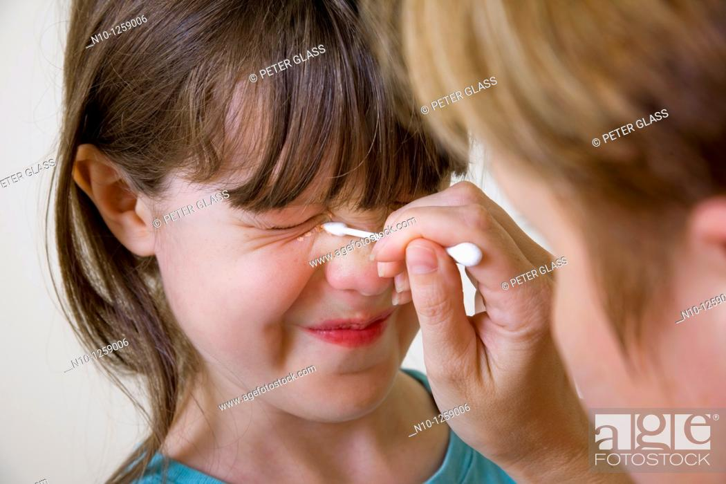 Stock Photo: Mother applying makeup to her daughter's face.