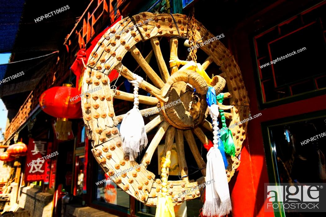 Stock Photo: Chinese lanterns and wheel at a market stall, HohHot, Inner Mongolia, China.