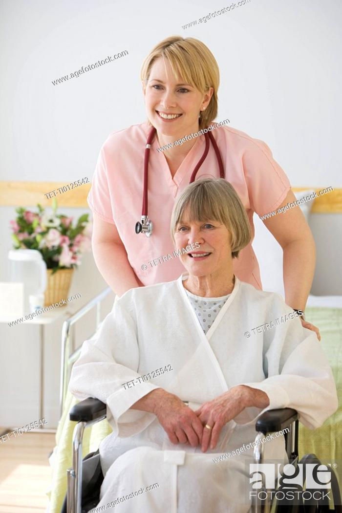 Stock Photo: Nurse pushing senior woman in wheelchair.