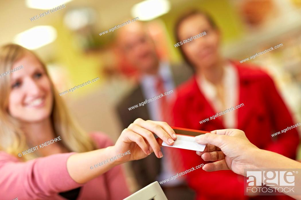 Stock Photo: Germany, Cologne, People using credit card in supermarket.