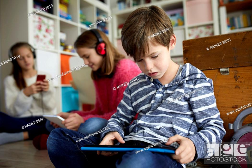 Imagen: Siblings playing at home with their digital tablets, sitting on ground.