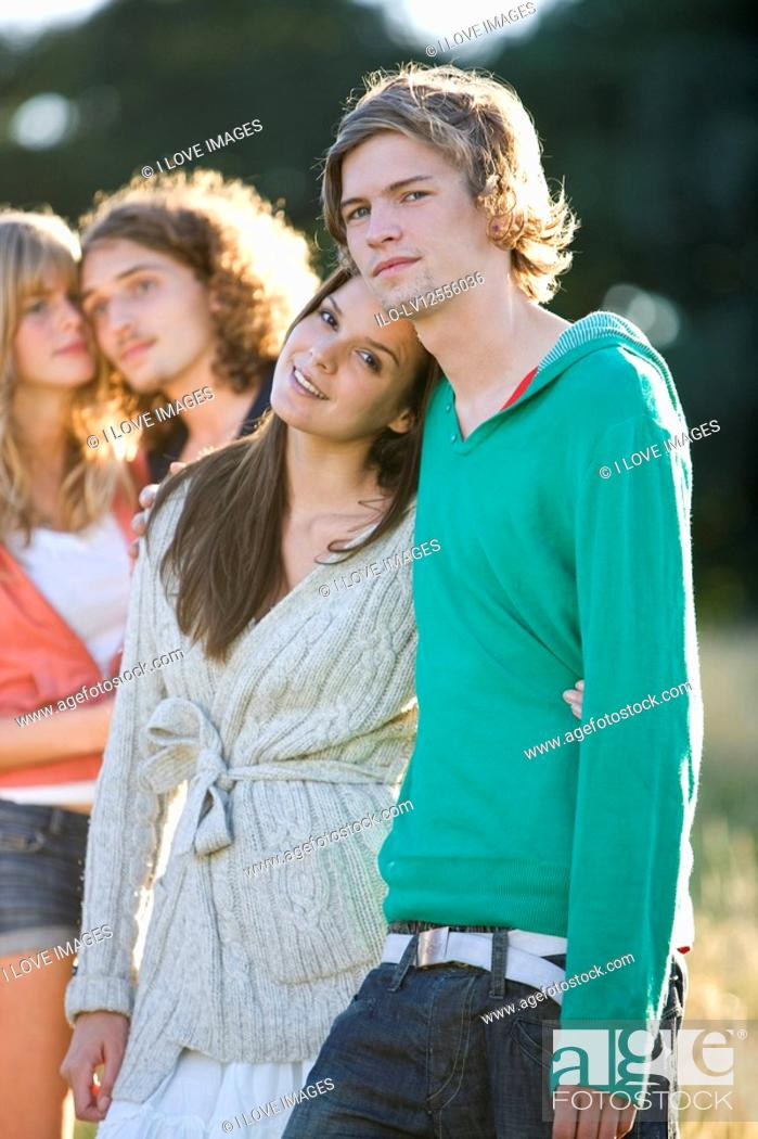 Stock Photo: Two young couples standing in a field.