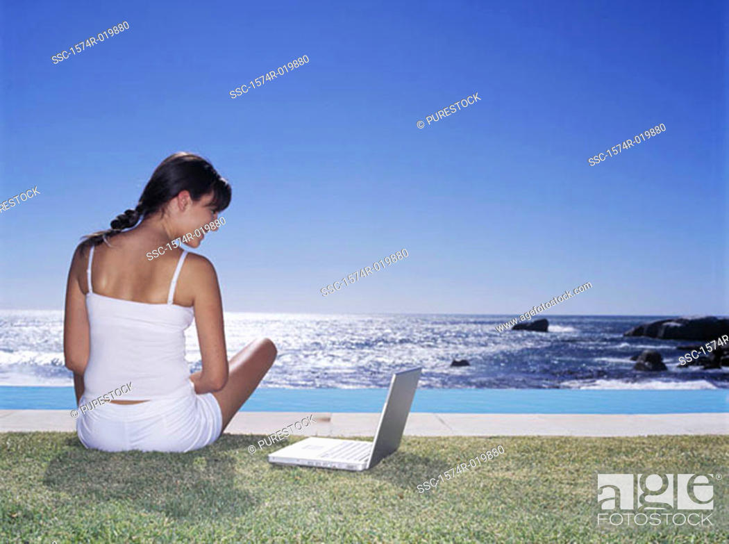 Stock Photo: Rear view of a young woman looking at a laptop.