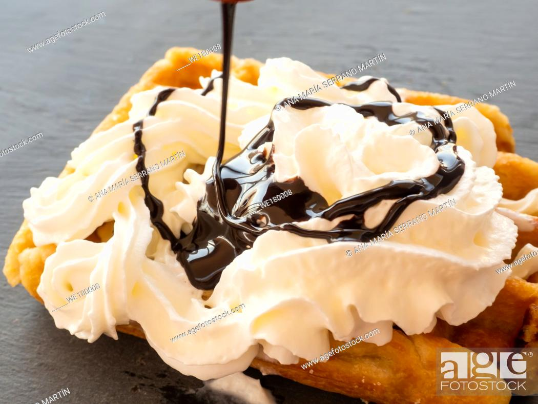 Imagen: Chocolate syrup falling on a Belgian waffle with cream on a slate plate.