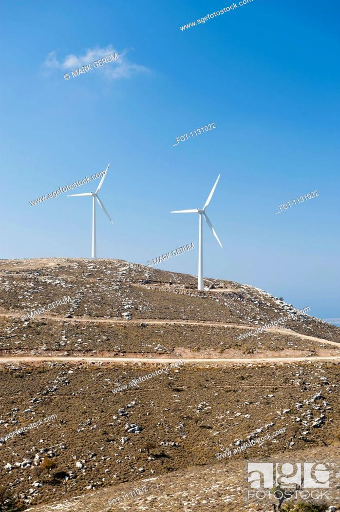 Stock Photo: Two wind turbines on a hill, Rhodes, Greece.
