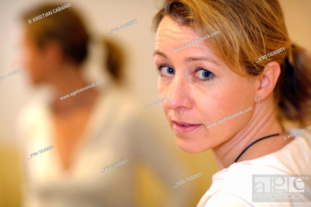 Stock Photo: Yong caucasian woman with long blond hair looking back over her shoulder, surprised, with her blurred image in the mirror, Hamburg, Germany, Europe.