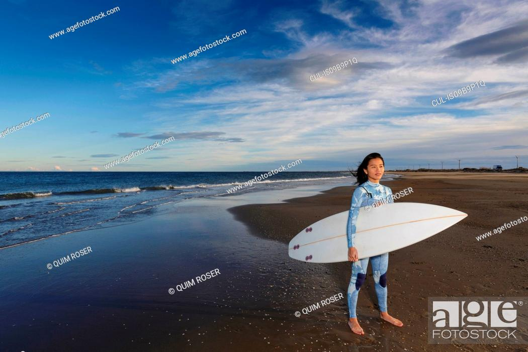 Stock Photo: Portrait of young female surfer standing on beach, Tarragona, Catalonia, Spain.