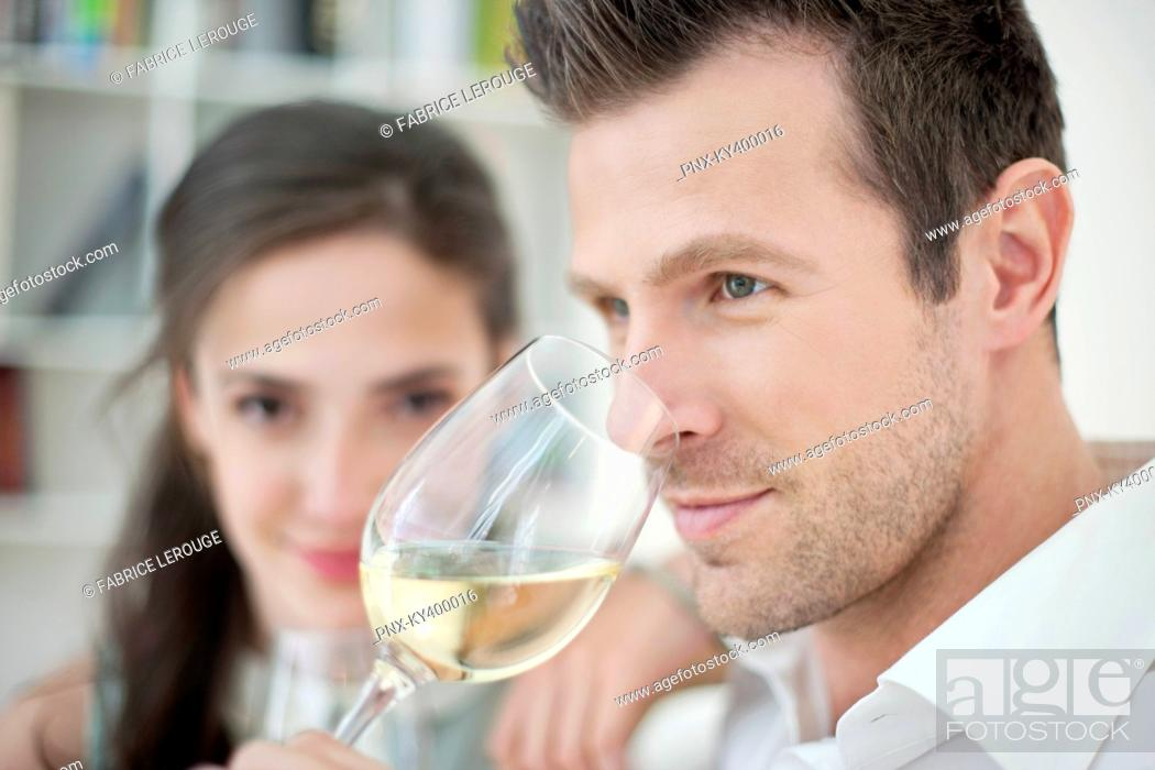 Stock Photo: Man drinking white wine with his wife in the background.