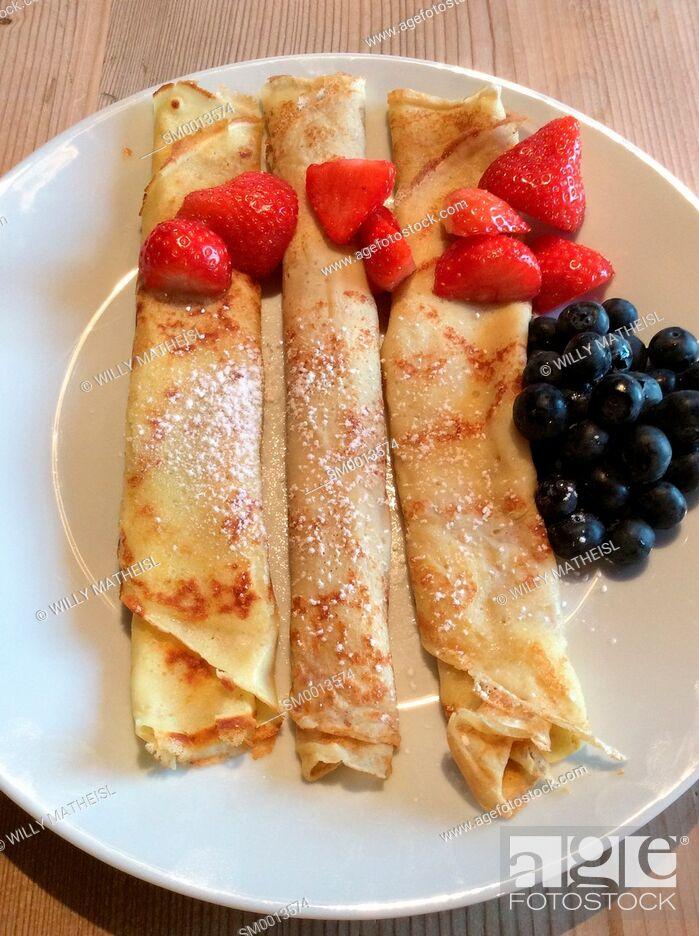 Stock Photo: Homemade Bavarian pancakes with strawberries, sugar powder and fresh blueberries.