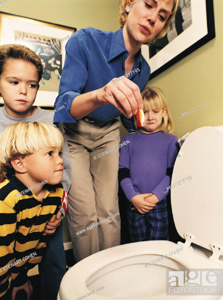 Stock Photo: Mother Holding Dead Goldfish over Toilet as Children Watch.
