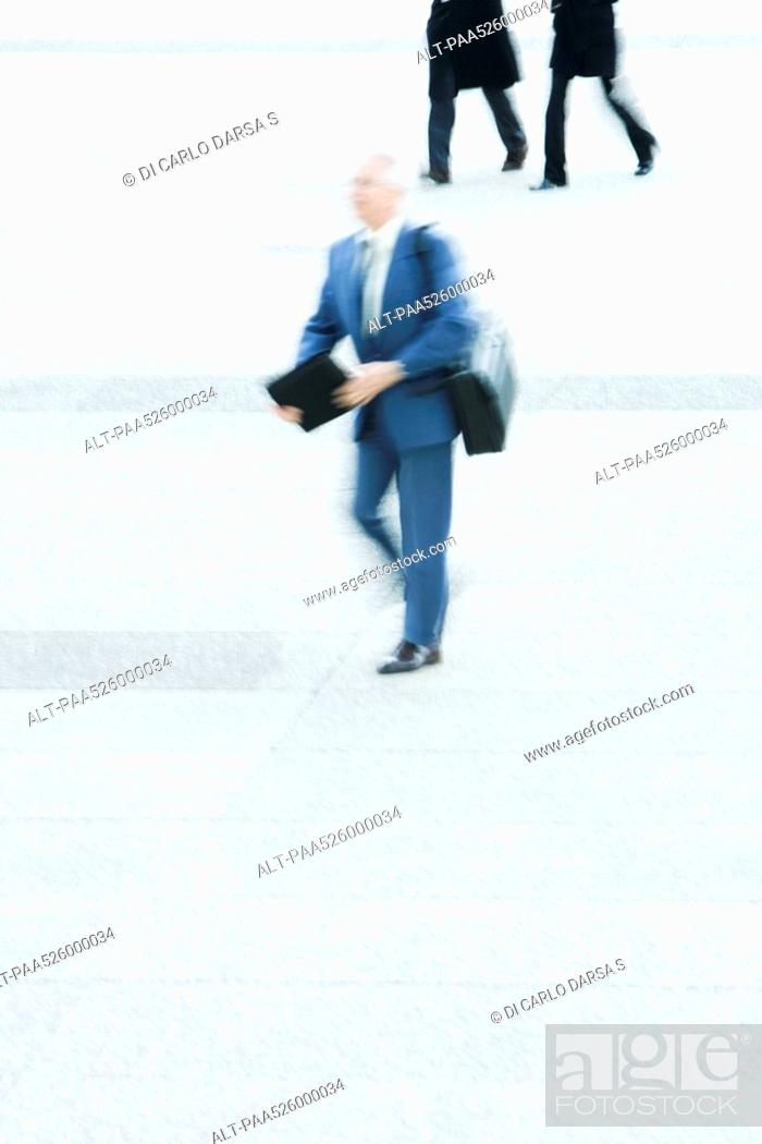 Stock Photo: Businessman carrying briefcase crossing public square.