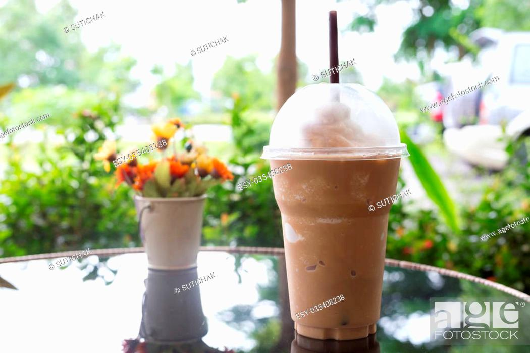 Stock Photo: cold ice coffee drink put on glass table in the garden.