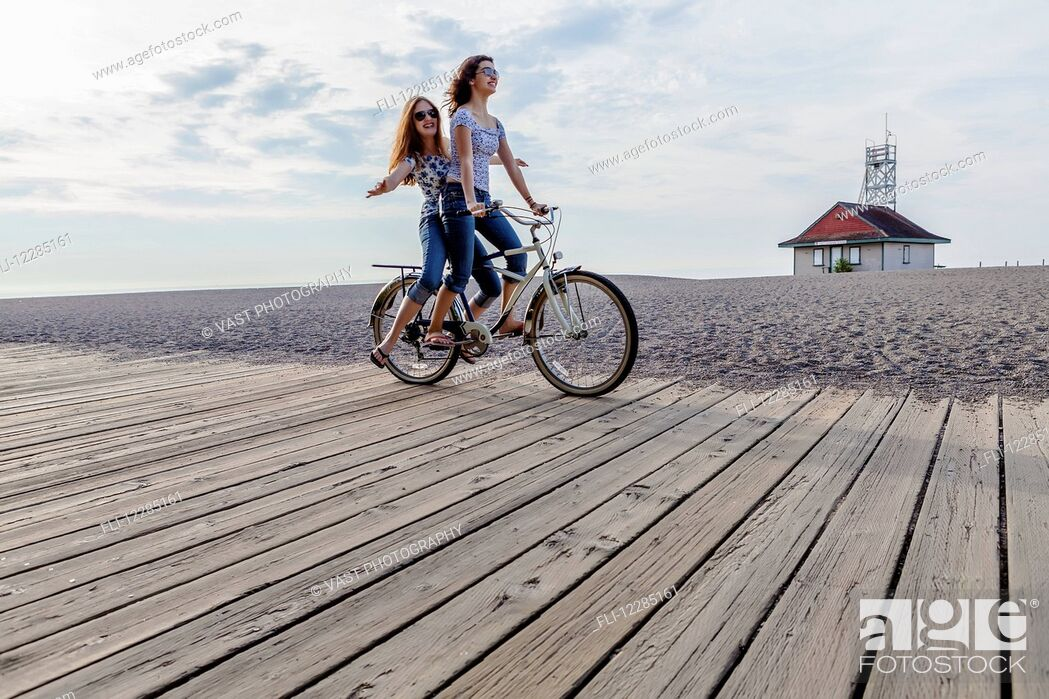 Stock Photo: Two girls riding double on a single bike on a beach boardwalk; Toronto, Ontario, Canada.